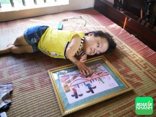 Cô gái Cao Thị Út cao 60 cm bên bức tranh giấy do chính tay mình tự làm.